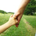gentle parental hands holding a child's hand for child custody attorneys Southfield