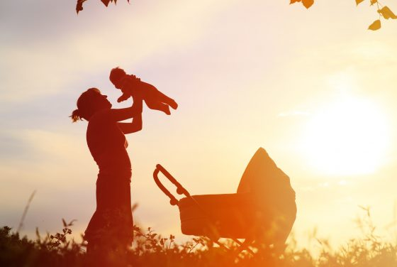 Silhouette of mother who called a bloomfield hills domestic violence attorney with little baby and stroller at sunset sky