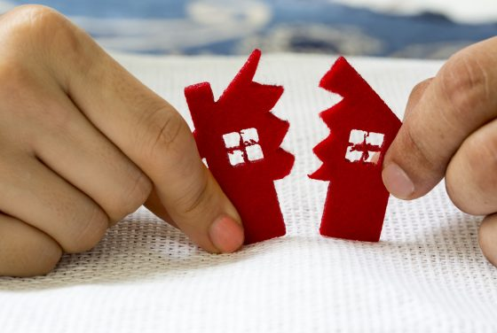 divorce concept for a wayne county divorce lawyer of a little red house being split in half by hands