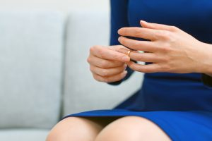 woman in blue dress taking off her wedding ring for a divorce attorney royal oak