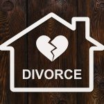 Paper house with the word divorce on it and if you need a divorce attorney find one in Bloomfield Hills.
