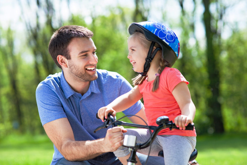 Dad with daughter learning how to ride a bike during his parenting time allotted from a family law lawyer in Sterling Heights