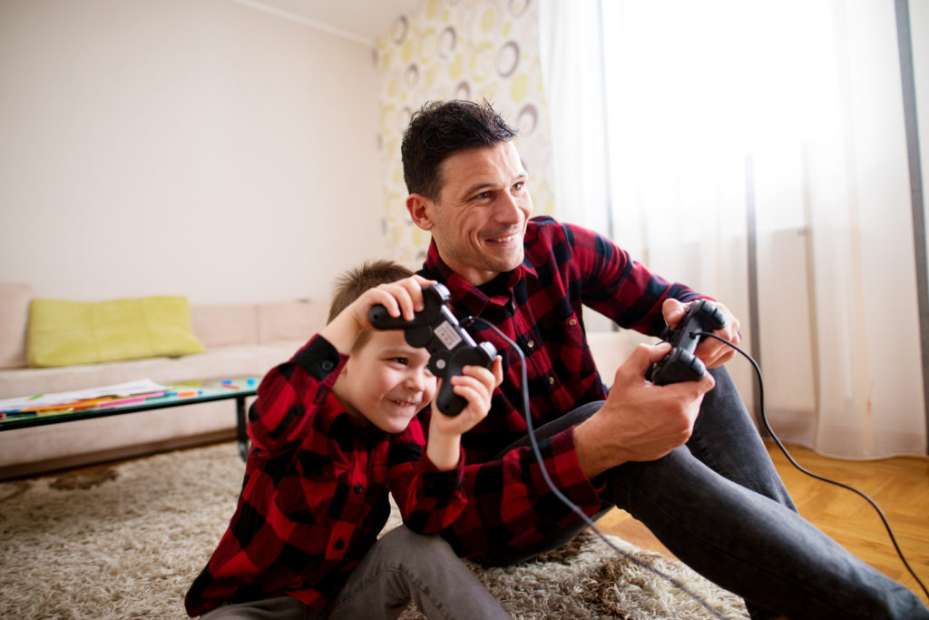 a young dad playing video games with his son, for when going through divorce seek a good family law attorney in Troy